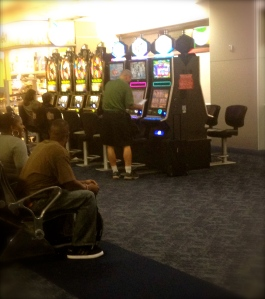 The crowded concourse in the Las Vegas airport overflows with slot machines.