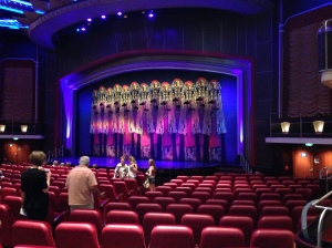 The audience begins to gather in a theatre similar to the Picardy Pavilion.